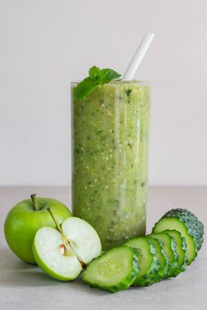 Green cucumber and apple smoothie in a glass, sliced ingredients on a light background