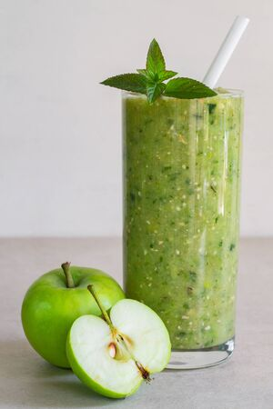 Green apple smoothie in a glass, whole and half apple on a light background