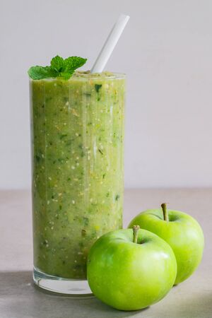 Green apple smoothie in a glass and two whole apples on a light background Stock Photo