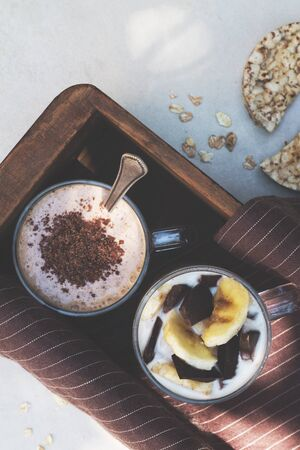 Two glass cups with ingredients banana, chocolate, oatmeal and yogurt and cooked smoothie in a wooden box. Top view