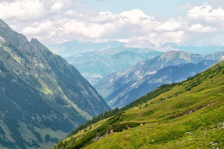 Panorama of picturesque blue mountainsides and green alpine meadows, Austrian Alps