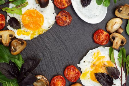 Nutritious breakfast of fried eggs, tomatoes, mushrooms with basil and microgreen on a black serving board