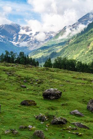 Picturesque alpine valley with large stones and green grass and mountains in the clouds. Austrian Alps