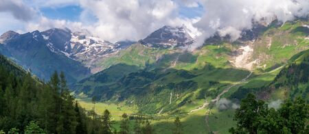 Picturesque panorama with green valleys, high firs and snow-covered mountains in clouds, Austrian Alps Фото со стока