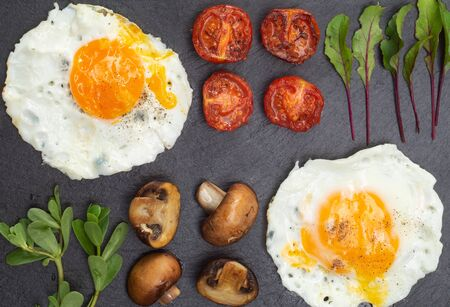 Nutritious breakfast of fried eggs, tomatoes, mushrooms with purslane and microgreen on a black serving board