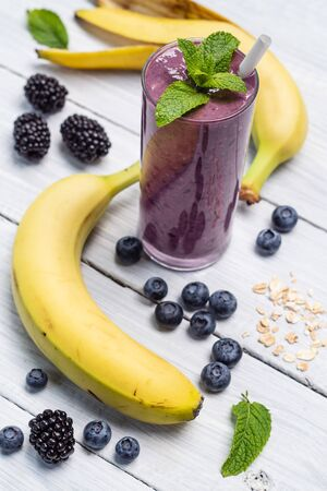 Smoothies of banana, blueberry, blackberry, oatmeal and yogurt in a glass on a white table and ingredients. Healthy breakfast Zdjęcie Seryjne