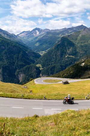 Motorcyclist on Grossglockner High Alpine Road, scenic tourist route in Austrian Alps Фото со стока
