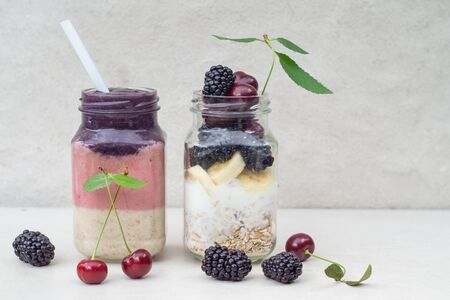 Three-layer smoothie of cherry, banana and blackberry with yogurt and oatmeal and ingredients in two glass jars