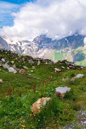 Picturesque alpine valley with large stones and green grass and mountains in clouds. Austrian Alps