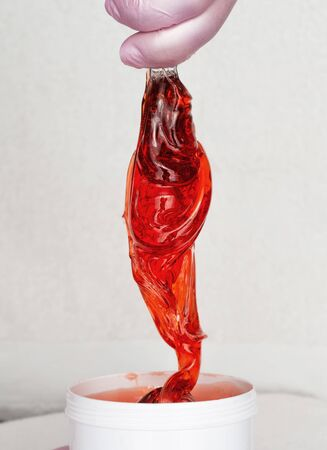 Beautician takes red transparent shugaring paste from a white can. Body care Zdjęcie Seryjne