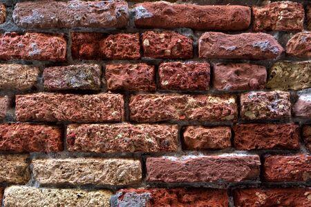 Old brick wall of red and yellow bricks Фото со стока
