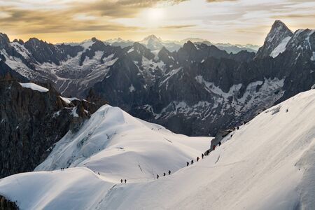 Climbers chain on a snowy mountainside of Mont Blanc Massif. Tourist destination, mountaineering
