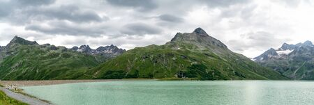 Panorama of lake Silvretta Stausee, mountain range and thunderclouds, Austrian Alps