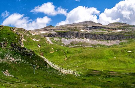 Green meadow and scenic mountainsides along Grossglockner High Alpine Road, Austrian Alps