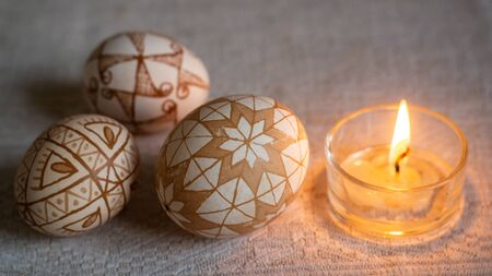 Traditional Ukrainian Easter eggs hot wax painted and a burning candle Banco de Imagens