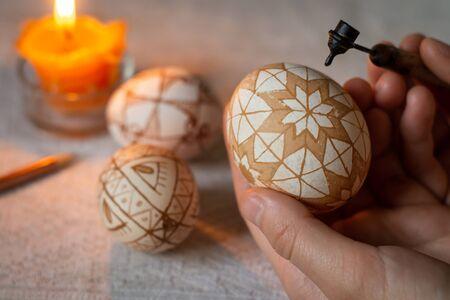 Ukrainian pysanka. Woman paints an Easter egg by hot wax