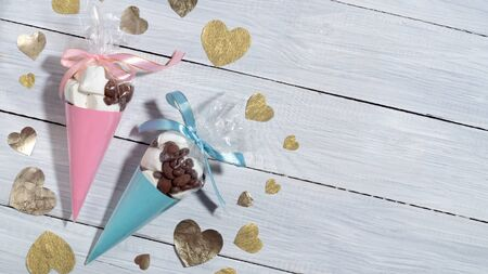 Valentine's Day. Blue and pink presents of sweets and marshmallows packed in cones