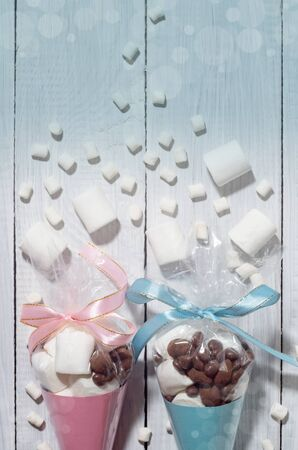 Blue and pink presents of candies and marshmallows packed in cones Standard-Bild