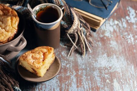 Cottage cheese casserole, cup of tea and a woolen scarf on a wooden table. Retro style