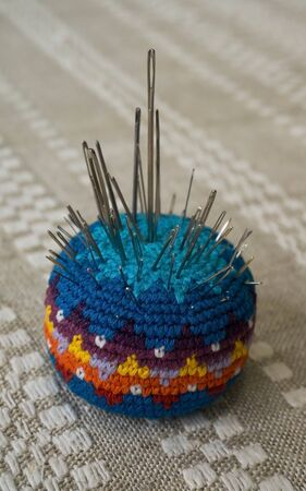 Knitted handmade needle bed with a lot of sewing needles on a linen tablecloth Stockfoto