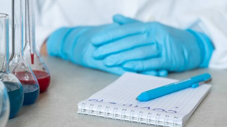 Covid-19. Hands of a chemist or virologist, notebook with pen and reagents in flasks in a laboratory 写真素材