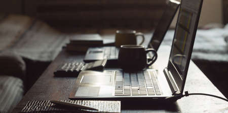 Home office concept. Two laptops and cups of coffee on a table indoors Archivio Fotografico