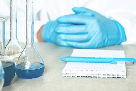 Hands of a chemist or virologist, notebook with pen and reagents in flasks in a laboratory
