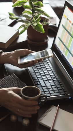 Home office concept. Woman working on a laptop, holding a smartphone and cup of coffee in her hands