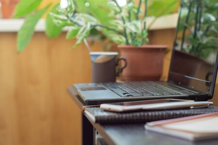 Laptop, smartphone and cup of coffee at home workplace. Home office of freelancer