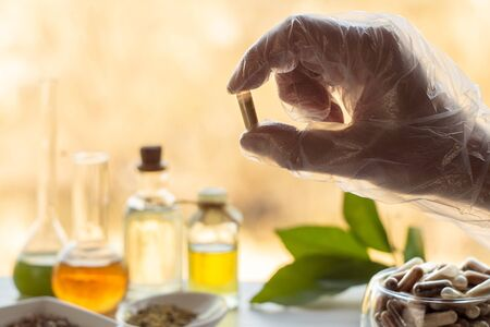 Hand of a pharmacist holds a capsule with dietary supplements on the background of jars of ingredients