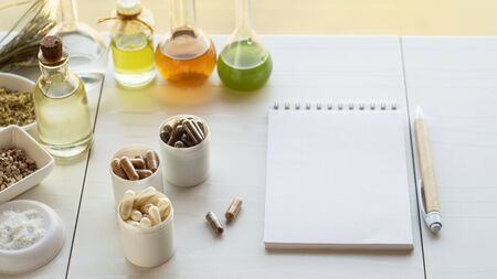 Various capsules with dietary supplements, ingredients for their creation and a notebook with a pen. Copyspace Фото со стока