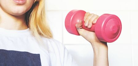 Young blonde girl holding a pink dumbbell in her hand, close-up. Doing sports at home