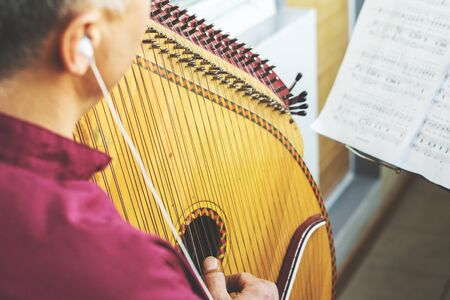 Male musician playing the bandura, rehearsing at home. Pandora is a traditional Ukrainian musical instrument