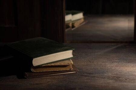 Three old books on a wooden table are reflected in an old mirror