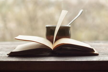 Cup of coffee and an open old book on a wooden windowsill. Retro style