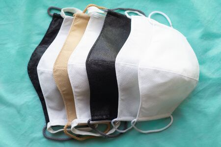 Stack of homemade protective reusable antiviral masks on green cloth