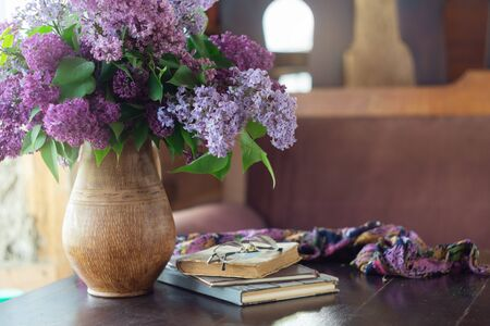 Lilac bouquet, сup of coffee, old books and glasses on table. Retro style