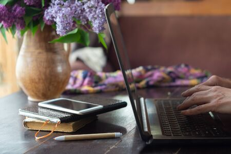 Home office concept. Woman working on a laptop near with a bouquet of lilacs