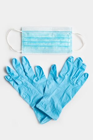 Protective antiviral concept. Blue gloves and a disposable mask. Top view Фото со стока