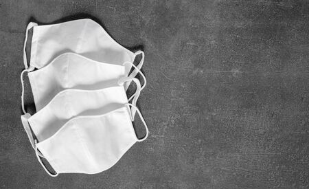 Stack of homemade protective reusable antiviral masks on black background