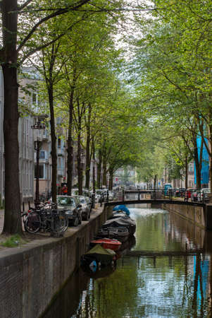 Bicycles, cars and boats on a city canal in Amsterdam, Netherlands 版權商用圖片