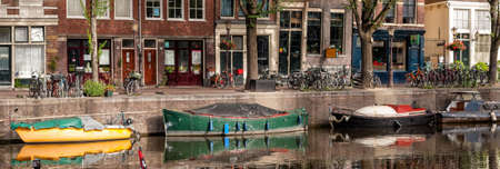 Old boats moored along a city canal in the background of a street in Amsterdam, Netherlands