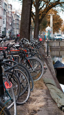 Bicycles parked near a city canal in Amsterdam, Netherlands
