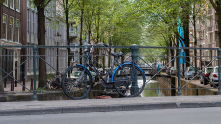 Bicycle parked near a city canal in Amsterdam, Netherlands