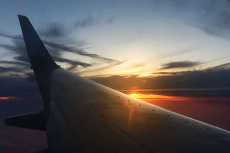 Wing of a flying airplane on the background of the sun rays at sunset or sunrise