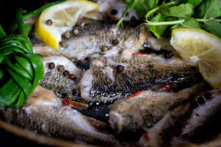 Raw small river fish with onions, lemon, herbs, pepper and salt, prepared for frying