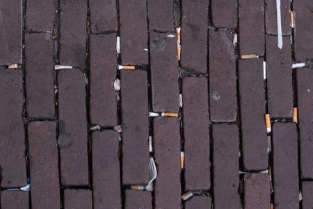 Paving stones on the street with many cigarette butts and plastic trash. Top view
