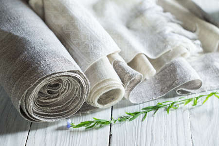 Old homespun and modern factory linen fabrics in rolls and blooming flax on a white wooden table Archivio Fotografico