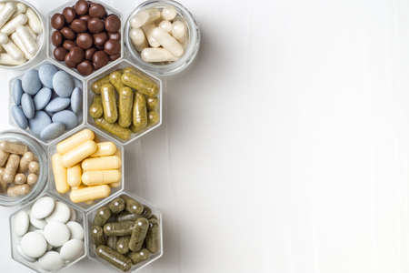 Various capsules and pills with dietary supplements or medicines in hexagonal jars Archivio Fotografico