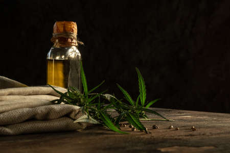 Hemp oil, textile and cannabis plant on wooden table